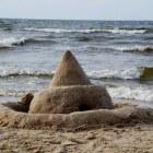 Zandkasteel op het strand en zandsculptuur
